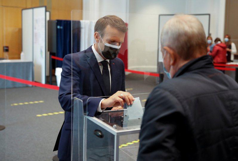 法國20日舉行地方選舉首輪投票,總統馬克宏在北部城市的一個投票站投票。(歐新社)