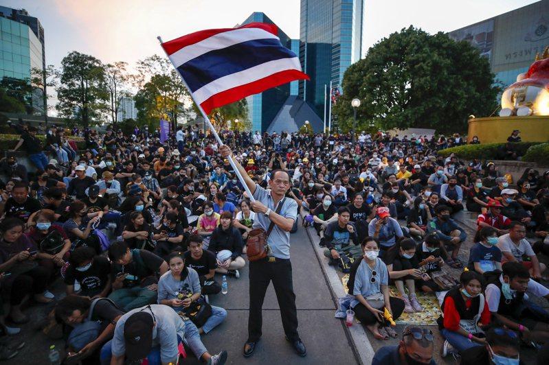 泰國自去年開始,由年輕人領導的示威活動對君主制度帶來前所未有的抨擊,圖為一名抗議者去年11月在曼谷一場活動中,揮舞著泰國國旗。(歐新社)