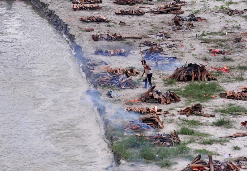 印度近日迎來雨季,恆河從上游沖刷出大批確診死者遺體,過去3周已有多達150具。圖為地方官員準備將打撈起來的遺體就地火化。 (路透)