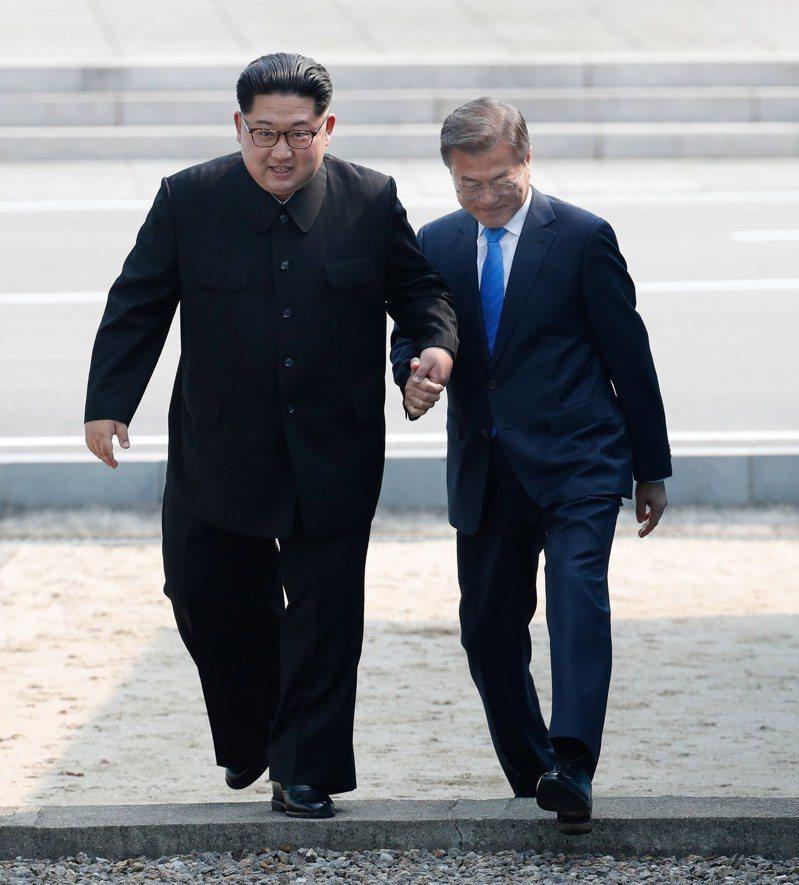 圖為2018年4月27日兩韓峰會當天,南韓總統文在寅(右)和北韓領導人金正恩(左)攜手跨過軍事分界線。(歐新社)