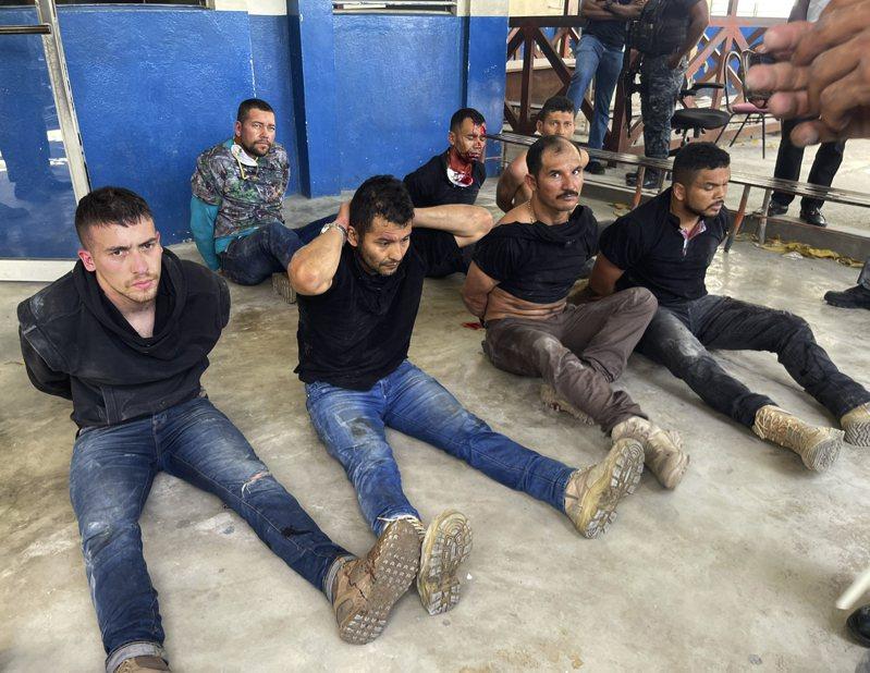 海地警方逮捕了刺殺總統摩依士的嫌犯,強制押坐於地。(美聯社)