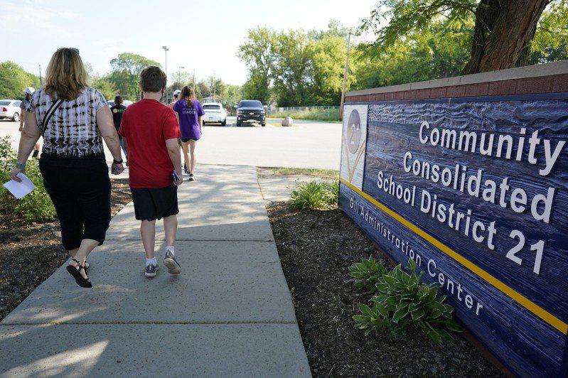 已有七州立法禁止公立學校強迫學生接種疫苗。圖為伊利諾州一處公立學校家長與學生同時接種。(美聯社)