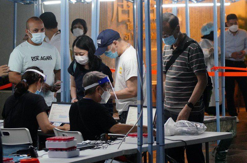 香港20日有七輸入確診個案,由於有確診個案曾居社區,跑馬地太古城兩廈強檢。圖為太古城金殿台唐宮閣居民晚間準備接受檢測。(中新社)