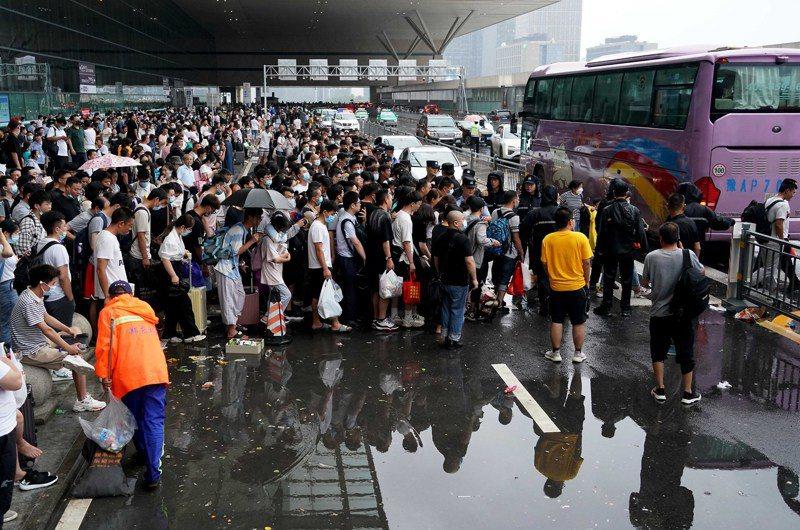 河南連日遭遇暴雨襲擊,7月21日,滯留旅客在鄭州東站進站口處排隊登乘大巴車。(新華社)
