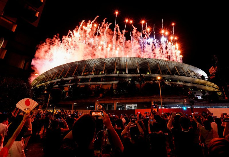東京時隔57年再度舉辦奧運會,卻因為新冠疫情,失去了應有的歡欣與希望;圖為23日晚的奧運開幕式,許多東京市民在體育場外觀看煙花。(路透)。