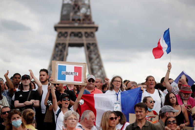 法國巴黎民眾24日上街反疫苗通行證。(路透)