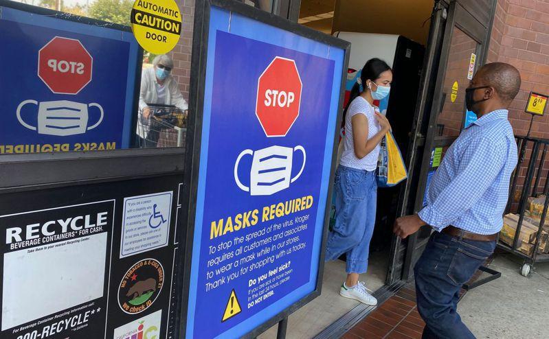 由於變種病毒肆虐,多地又開始實施口罩令。圖為洛杉磯的超市推出告示,要求顧客必須戴口罩。(Getty Images)