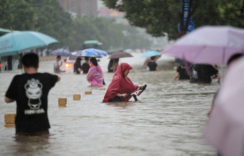 近期世界各地出現的災難性天氣,例如河南鄭州的洪災等,更凸顯解決氣候變暖問題刻不容緩。圖為鄭州民眾在暴雨中涉水前行。(路透)