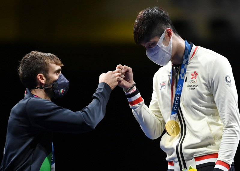 男子個人花劍金牌得主中國香港選手張家朗(右),與銀牌得主義大利選手加羅素擊拳致意。(新華社)