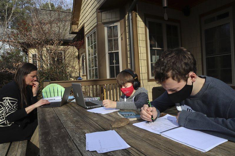 擔心網課造成小孩學業退步,密西西比州一個媽媽在家督促孩子寫功課。(美聯社)