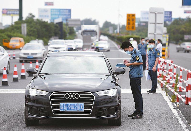 多地嚴防市民離開本地,紛紛在進出城道路設卡攔查,圖為南京寧洛高速公路曹莊收費站,執法人員勸返不符合離城條件的車輛。(新華社)