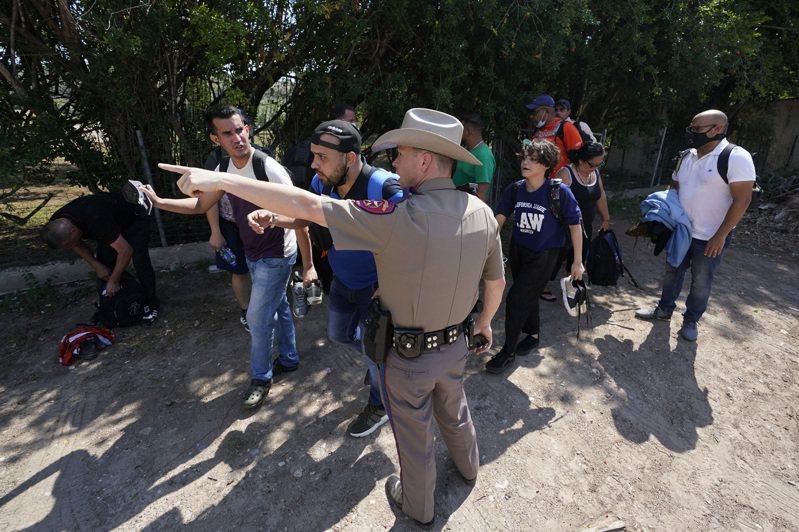 邊界執法人員在德州德爾里奧戒護一批非法越界的無證移民至拘留中心。(美聯社)