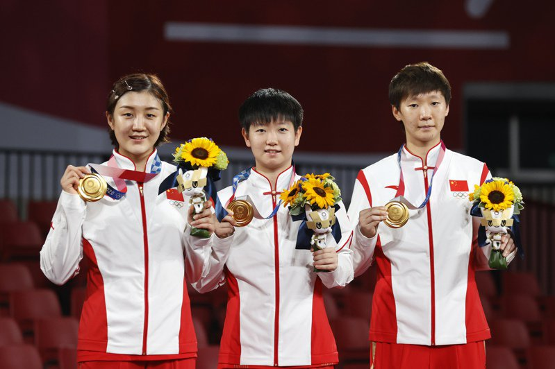 東京奧運乒乓球女團賽,中國隊3比0完勝日本隊摘金,取得奧運四連冠,陳夢(左起)、孫穎莎、王曼昱展示金牌。(中新社)