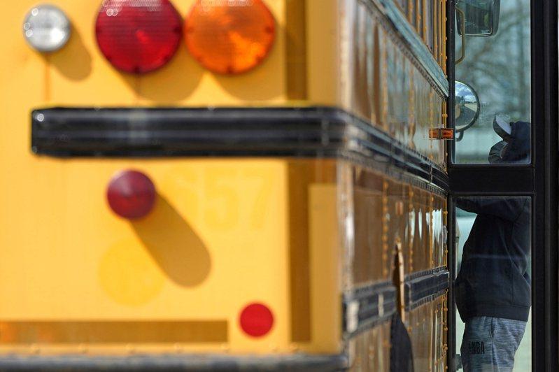伊利諾州一名工作人員搬運給學童的餐點。(美聯社)